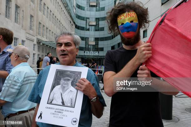Protester is seen wearing a mask with the Colombian flag colors writes on top Asesinos while an other carry a picture of Gilberto Antonio Zuluaga...