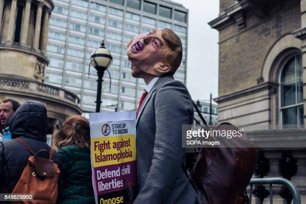 A protester is seen wearing a Trump mask on his face during the rally against US president Donald Trump Following various incidents postBrexit and...