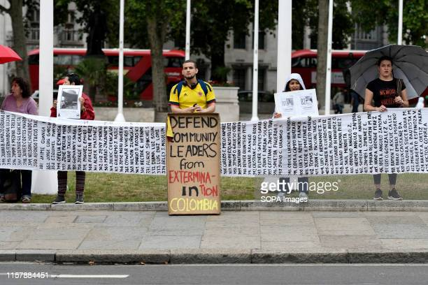 A protester is seen wearing the Colombian national football team shirt while holding a placard that reads Defend community leaders from extermination...
