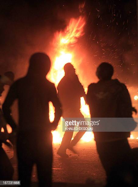A protester is silhouetted by the flames of a burning police truck during clashes with riot police at Cairo's landmark Tahrir Square on November 19...