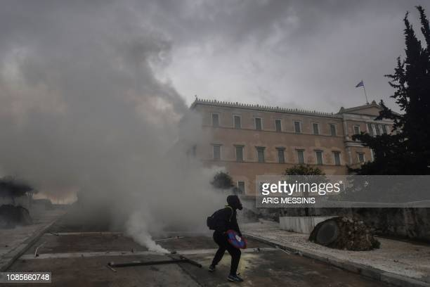 A protester is surrounded by smoke in Athens on January 20 2019 during a demonstration against the agreement with Skopje to rename neighbouring...