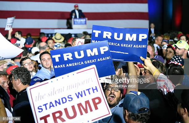 TOPSHOT A protester is surrounded by Trump supporters as he tries to disrupt a rally for Republican presidential candidate Donald Trump on March 13...