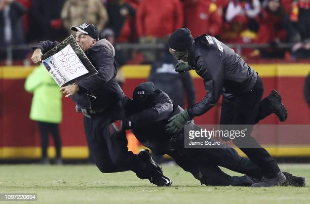 A protester is tackled by security after running on the field during the AFC Championship Game between the Kansas City Chiefs and the New England...