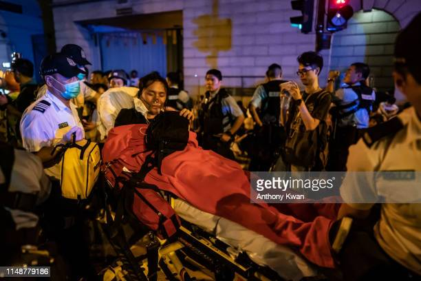 A protester is taken away after being injured during a clash at Legislative Council after a rally against the extradition law proposal at the Central...