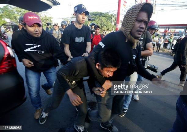Protester is taken away by plainclothes police in front of the Hasanuddin University campus in Makassar, Sulawesi on September 26 during a rally...