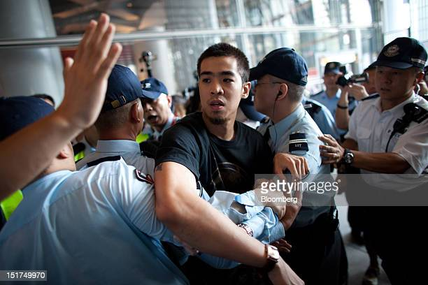 Protester is taken away by security guards at the Occupy Central camp in the plaza beneath HSBC Holdings Plc's Asian headquarters in Hong Kong,...