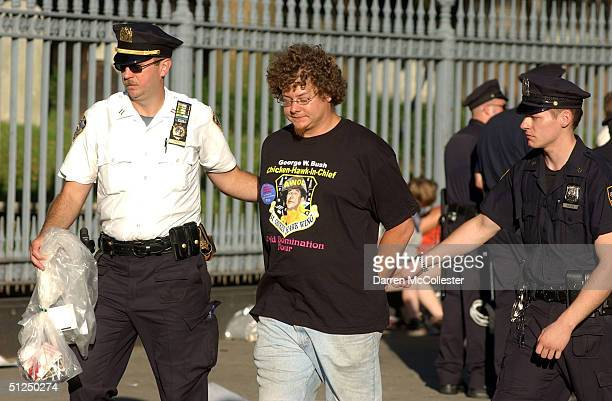 A protester is taken into custody after being arrested at the corner of Fulton and Church Street following an attempted march from Ground Zero to...