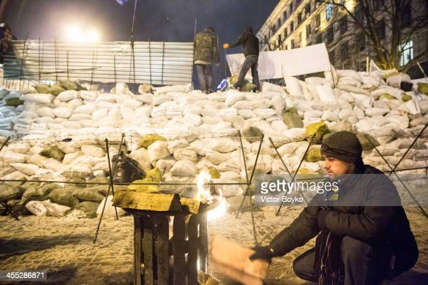 A protester is warming up himself while other protesters installing metal sheet barriers and barbed wire on a new reinforced barricade on Maidan...