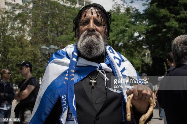 A protester is wearing a Greek flag and a cross at the rally Rally for the immediate release of two military personnel and the cessation of...