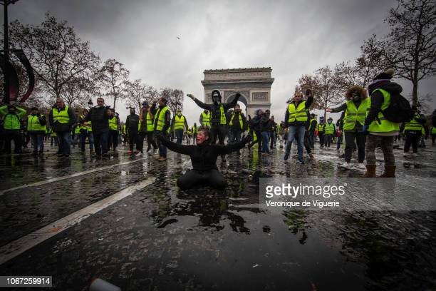 A protester is wounded by a water canon as they clash with riot police during a 'Yellow Vest' demonstration near the Arc de Triomphe on December 1...