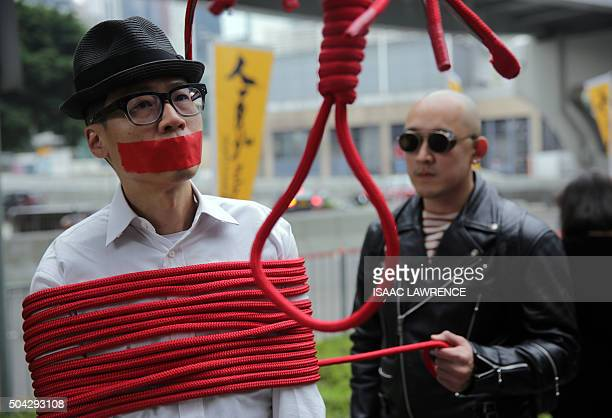 A protester is wrapped up with a rope made into a noose during a march calling for the release of missing booksellers from Hong Kong's Mighty Current...