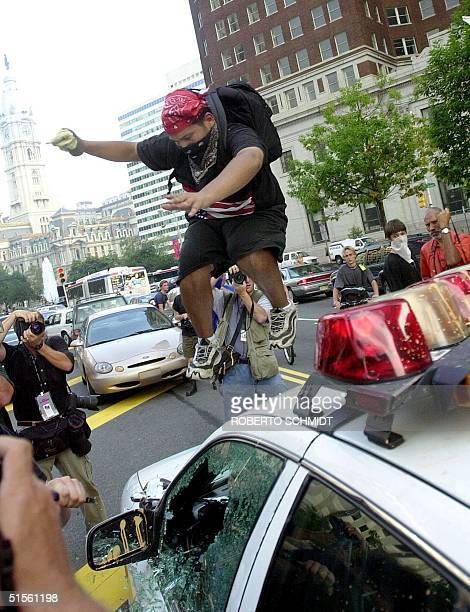 A protester jumps on the hood of a police car that was vandalized by angry demonstrators marching in downtown Philadelphia 01 August 2000 Thousands...