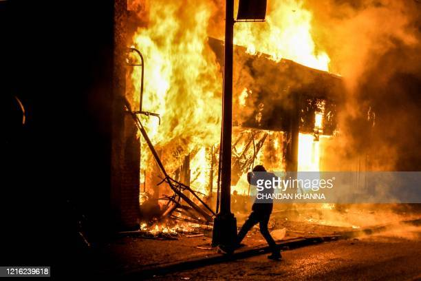 Protester kicks a stone into a burning building set on fire during a demonstration in Minneapolis, Minnesota, on May 29 over the death of George...