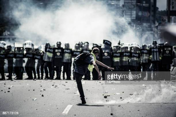 A protester kicks a tear gas canister back to the Bolivarian National Police during a demonstration to the streets of Caracas Venezuela on November...