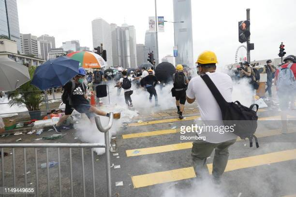 A protester kicks a tear gas cannister outside the Legislative Council during a protest against a proposed extradition law in Hong Kong China on...