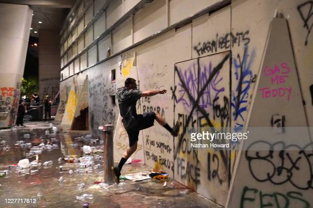 A protester kicks an entrance to the Mark O Hatfield US Courthouse after federal officers took shelter inside on July 21 2020 in Portland Oregon The...
