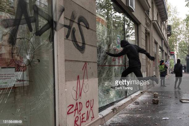 Protester kicks in a bank window at the International Labour Day protests on May 1, 2021 in Paris, France. Every year May Day is used to mark the...