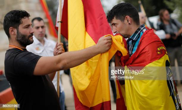 A protester kisses a Spanish flag during an ultraright wing antiseparatist demonstration for the unity of Spain called by 'Falange Espanola' during...