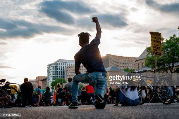 Protester kneels and holds up a fist as he and others demonstrate the death of George Floyd by closing down and blocking traffic on I-395 in...