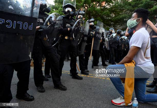 A protester kneels in front of a row of police during a demonstration against the death of George Floyd at a park near the White House on June 1 2020...