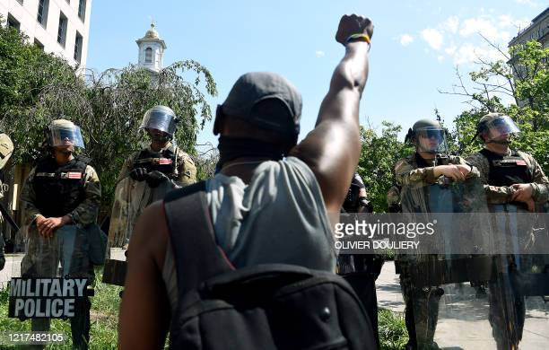TOPSHOT A protester kneels in front of military police near the White House to protest the death of George Floyd who died in police custody in...