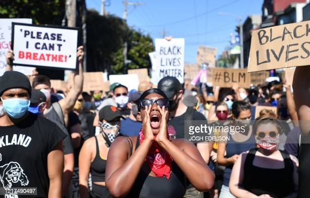 Protester leads a crowd in a back and forth chant during a rally in support of George Floyd and against police brutality at Dolores Park in San...