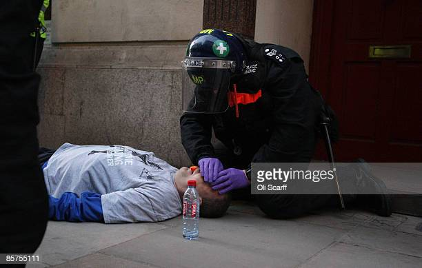 A protester lies injured after a confrontation with the police near to the Bank of England as anti capitalist and climate change activists...