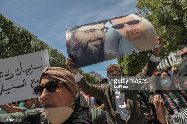 Protester lifts a poster with photo portrait of the Syrian President Bachar al-Assad and the leader of Hezbollah Hassan Nasrallah during a...