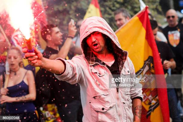 TOPSHOT A protester lights a flare during an ultraright wing antiseparatist demonstration for the unity of Spain called by 'Falange Espanola' during...