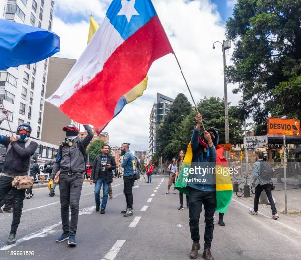 Protester loads the flag of Chile and Bolivia in the march during the national strike on December 19 2019 in Bogota Colombia