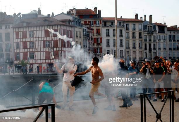 TOPSHOT A protester lobs a 'canister' back towards French security personnel during a demonstration in the city of Bayonne southwest France on August...