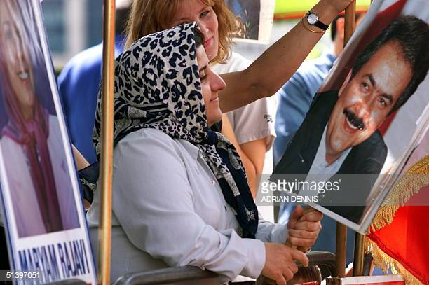 A protester looks admiringly at a placard of Masoud Rajavi husband of Iran's Resistance Presidentelect Maryam Rajavi during a demonstration about the...
