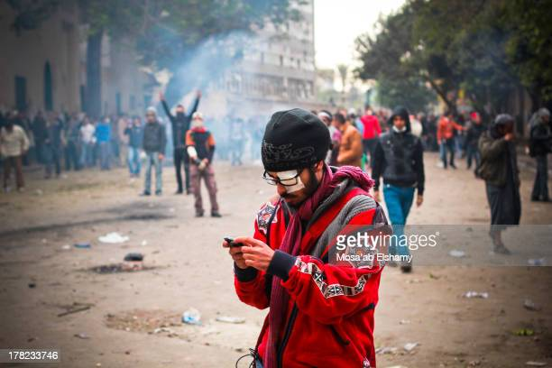 Protester looks at his mobile phone during clashes with security forces in Mohamed Mahmoud street.