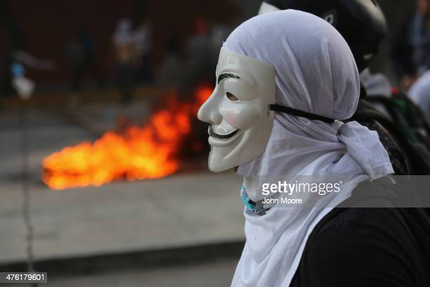 A protester looks at national guard troops during an antigovernment demonstration on March 2 2014 in Caracas Venezuela Venezuela has one of the...