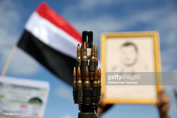Protester loyal to Houthi movement holds up his gun as he takes part in a protest held to mark the International Quds Day on May 31, 2019 in Sana'a,...
