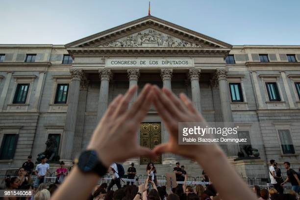 A protester makes a feminist symbol with her hands during a demonstration against the release of the 'La Manada' gang members outside of the Spanish...
