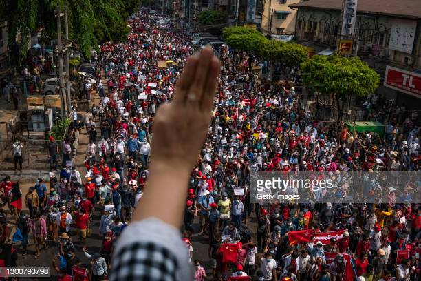 Protester makes a three-finger salute as others march on February 07, 2021 in Yangon, Myanmar. Some internet services were restored in Myanmar on...
