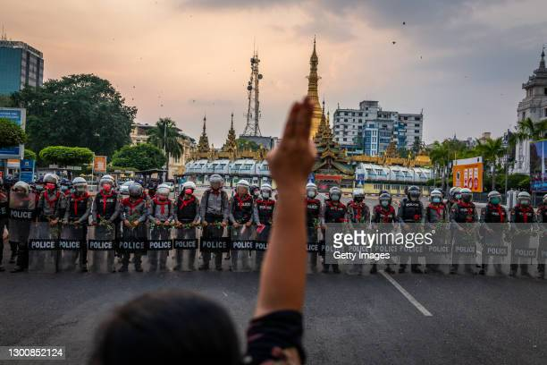 Protester makes a three-finger salute in front of a row of riot police, who are holding roses given to them by protesters, on February 06, 2021 in...