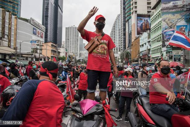 Protester makes a three-finger salute while standing on a motorbike during the car mob rally. Anti-government protesters gathered at Asok...