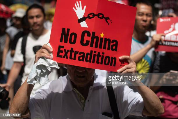 TOPSHOT A protester marches with a placard during a rally against a controversial extradition law proposal in Hong Kong on June 9 2019 Huge protest...