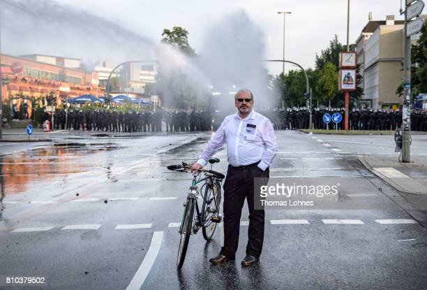 Protester Martin Friedrich Buehler walks with his bike between the police water cannon and violent demonstrators during during a demonstration...