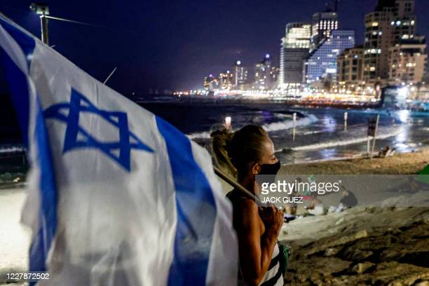 Protester, mask-clad due to the COVID-19 coronavirus pandemic, stands with an Israeli flag near a beach during a demonstration against the Israeli...