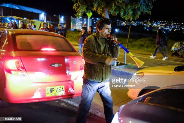 Protester moves with his trumpet between the blocked traffic on the north highway during protests and a national strike against the government of...