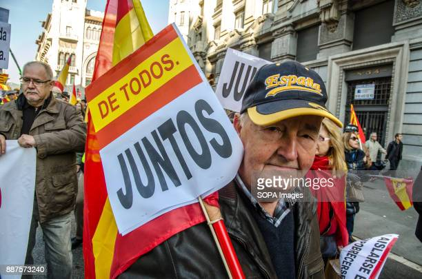 A protester of the Spanish unionism with a sign with the text 'all together' and a cap with the text Spain Spain celebrates today the 39 anniversary...
