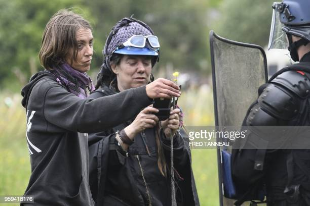 TOPSHOT A protester offers a flower to a French riot gendarme during a second eviction of environmental protesters from the area known as ZAD at the...
