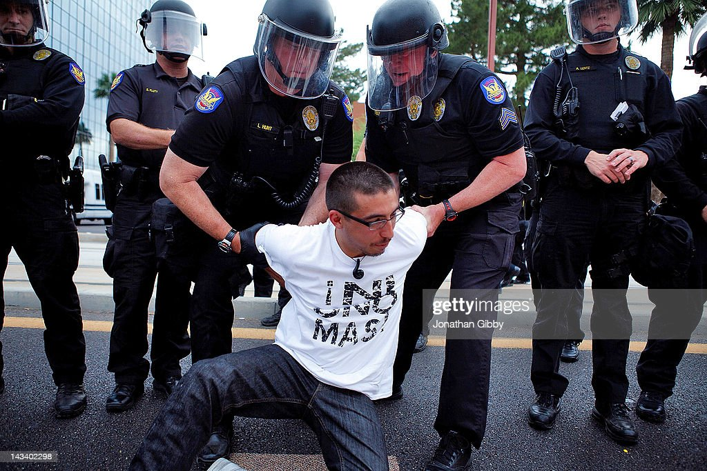 A protester opposed to Arizona's Immigration Law SB 1070 is taken into custody by police officers April 25, 2012 in Phoenix, Arizona. Immigrant rights advocates held a day of protest in Phoenix, the same day the U.S. Supreme Court heard arguments over Arizona's 2010 immigration enforcement law.