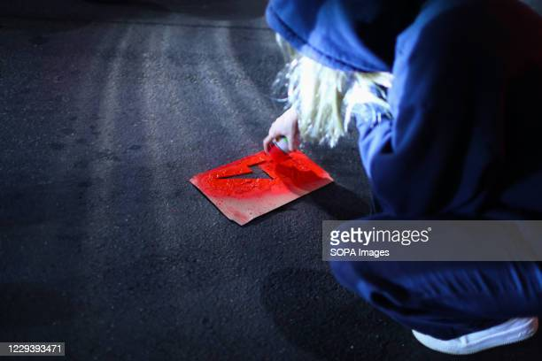 Protester paints on the street the symbol of the women's strike, red lightning, using a spray paint and a cardboard template during the...
