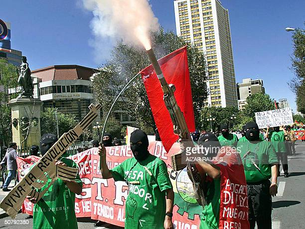 A protester part of a group of activists wearing balaclavas fires a rocket through a mock AKM rifle during a MayDay march in downtown La Paz Bolivia...