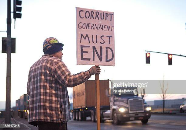 A protester participating in the Occupy the Ports event holds a sign as trucks prevented from entering Port take a detour December 12 2011 in...