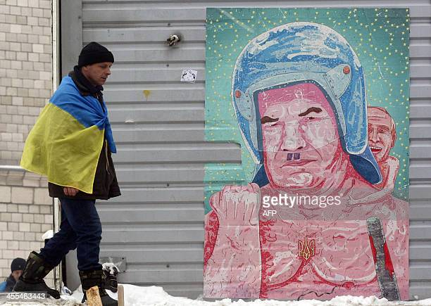 A protester passes graffiti depicting Ukrainian President Viktor Yanukovych wearing a riot helmet and wielding a bloody baton with Russian President...